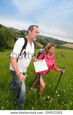 Senior couple hiking in natural landscape - stock photo