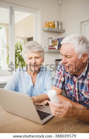 Senior couple holding a pill bottle and discussing while operating laptop - stock photo