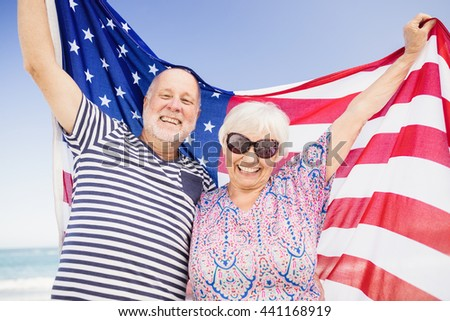 Senior couple holding american flag together on beach - stock photo