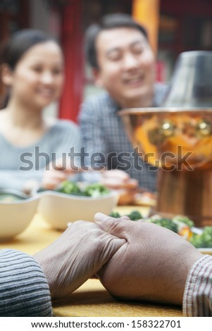 Senior couple holding hands at a family meal - stock photo