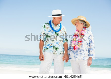 Senior couple holding hands on the beach on a sunny day - stock photo