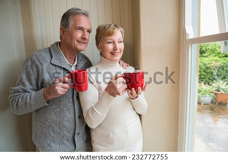 Senior couple holding red mugs at home in the kitchen - stock photo