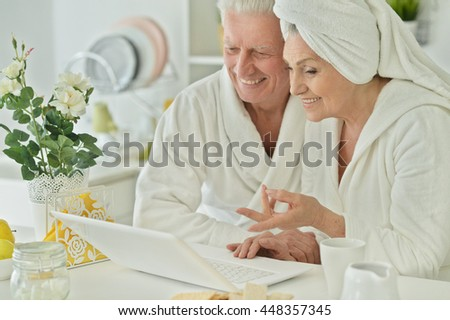 senior couple in a bathrobes with laptop
