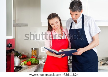 Senior couple in a kitching looking at cookbook - stock photo