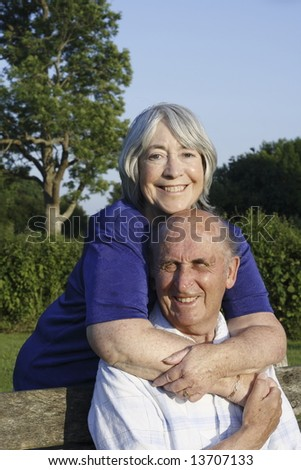 Senior couple in a park on a summers evening. - stock photo
