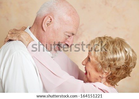Senior couple in a romantic embrace, looking deep into each other's eyes.