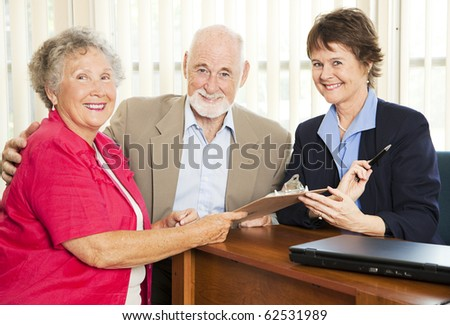 Senior couple in a sales woman or financial consultant's office. - stock photo