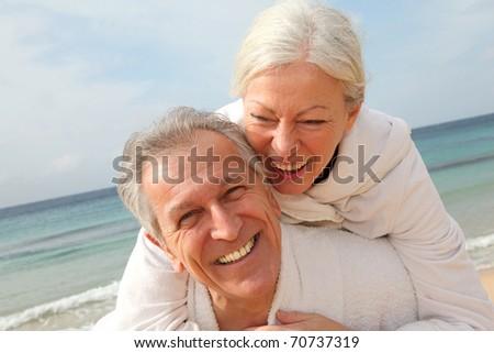 Senior couple in bathrobe at the beach - stock photo