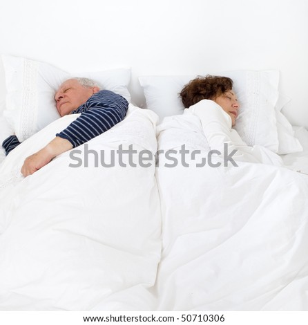 senior couple in bed asleep - stock photo