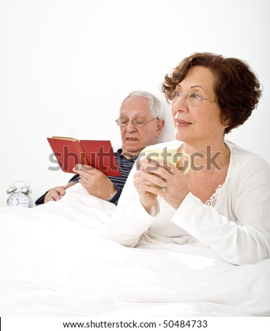 senior couple in bed man reading and woman having a cup of coffee - stock photo
