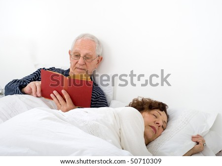 senior couple in bed man reading and woman is asleep - stock photo