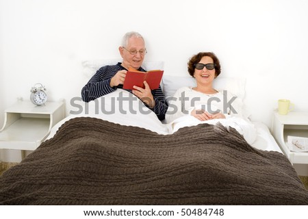 senior couple in bed man reading woman watching 3D TV with special glasses - stock photo