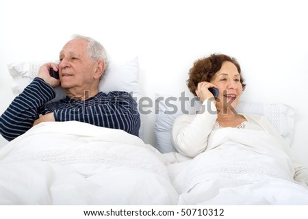 senior couple in bed talking on the phone - stock photo