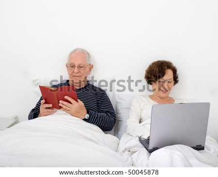 senior couple in bed with laptop and book - stock photo
