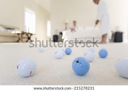 Senior couple in bedroom, man practising golf putt, focus on golf balls in foreground - stock photo