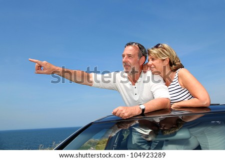 Senior couple in convertible car enjoying day trip - stock photo