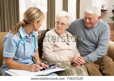 Senior Couple In Discussion With Health Visitor At Home - stock photo
