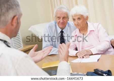 Senior couple in doctor's office - stock photo