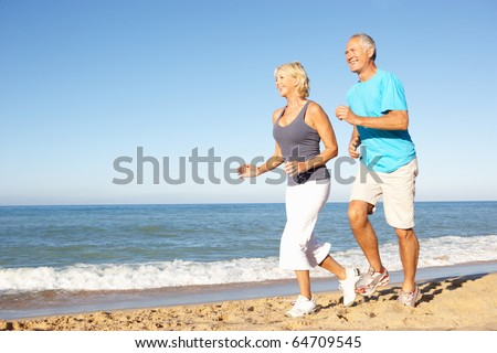 Senior Couple In Fitness Clothing Running Along Beach - stock photo