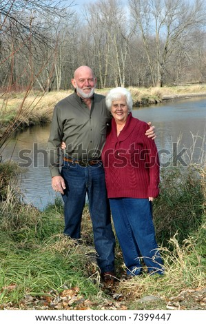 senior couple in front of a river - stock photo