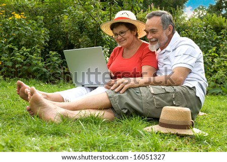 senior couple in garden at leisure with laptop computer - stock photo