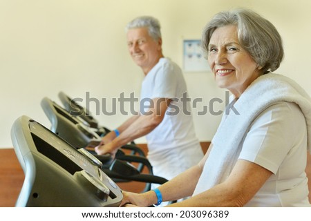 Senior couple in gym on running track - stock photo
