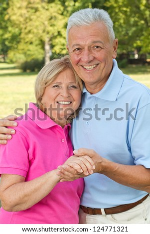 Senior couple in late sixties posing hugged showing love - stock photo