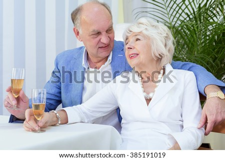 Senior couple in love drinking wine together in light interior