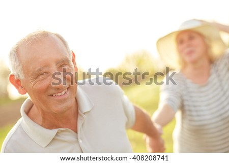 Senior couple in love holding hands and walking on countryside. - stock photo
