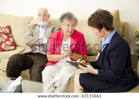 Senior couple in marriage counseling.  The wife talks while the counselor takes notes.