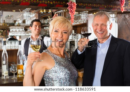 Senior couple in restaurant standing at bar with glass of wine in hand and having fun - stock photo