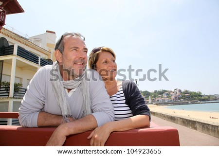 Senior couple in seaside resort looking at the beach - stock photo