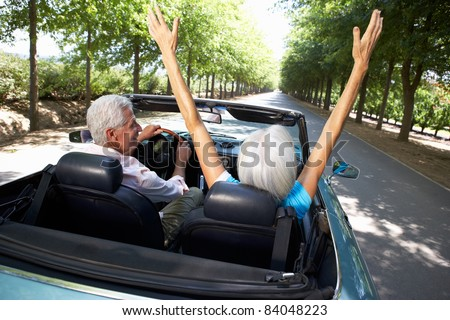 Senior couple in sports car - stock photo