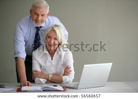 Senior couple in suit in front of a laptop computer - stock photo