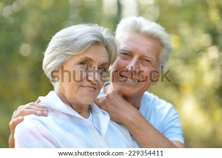 Senior couple in summer park on green background