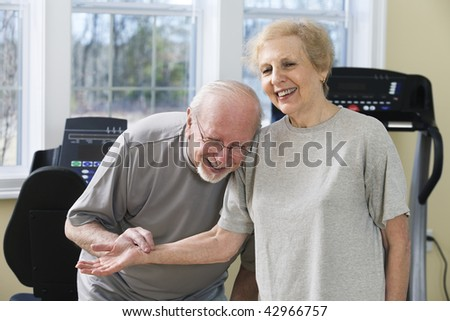 Senior couple in the gym. The man is checking the woman's pulse. Horizontally framed shot.