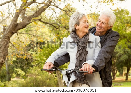 Senior couple in the park on an autumns day - stock photo