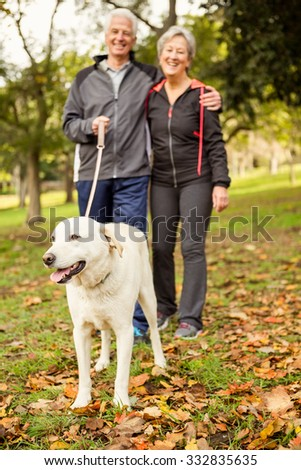 Senior couple in the park with dog on an autumns day - stock photo