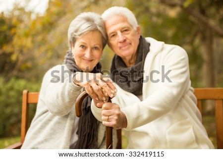 Senior couple in the parkon an autumns day - stock photo