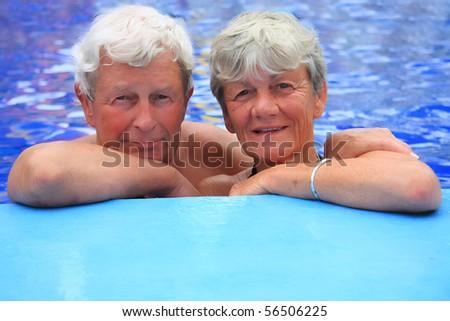 Senior couple in the swimming pool - stock photo