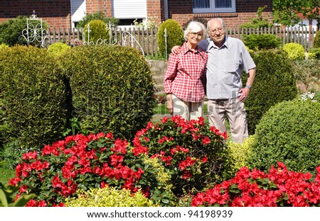 Senior couple in their garden with bushes and flowers - stock photo