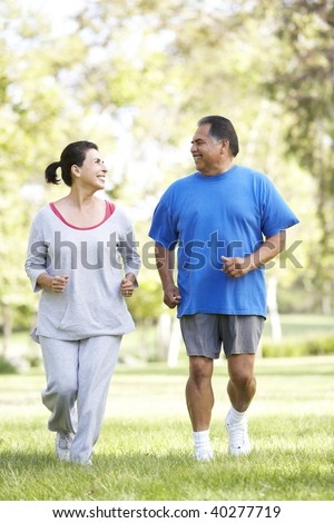 Senior Couple Jogging In Park - stock photo