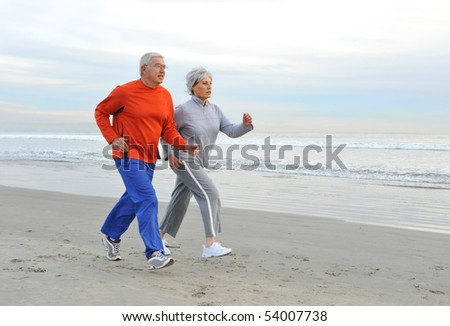 Senior couple jogging on the beach in the early morning - stock photo
