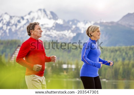 Senior couple jogging round the tarn in beautiful mountains, hills and hotel in background - stock photo