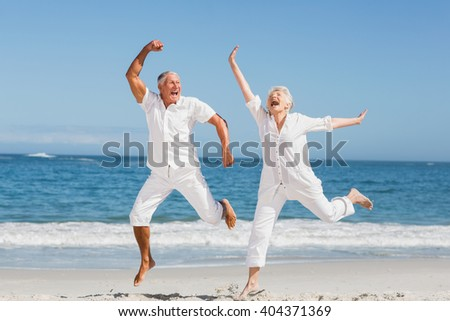 Senior couple jumping at the beach on a sunny day - stock photo