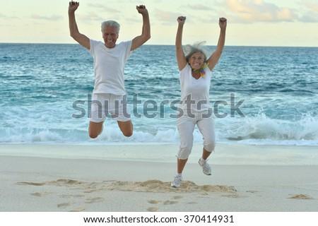 Senior couple  jumping on  seashore - stock photo