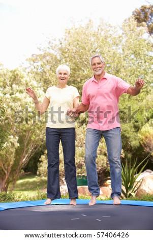 Senior Couple Jumping On Trampoline In Garden - stock photo