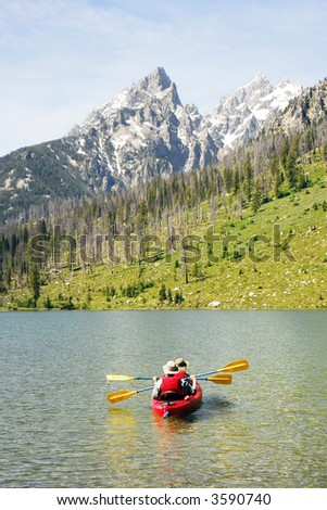 Senior couple kayaking with  mountains in the background - stock photo