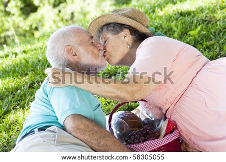 Senior couple kissing on a romantic picnic in the park. - stock photo