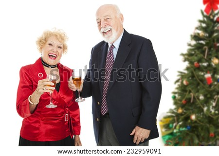 Senior couple laughing and drinking champagne at a Christmas party.  Isolated on white.   - stock photo